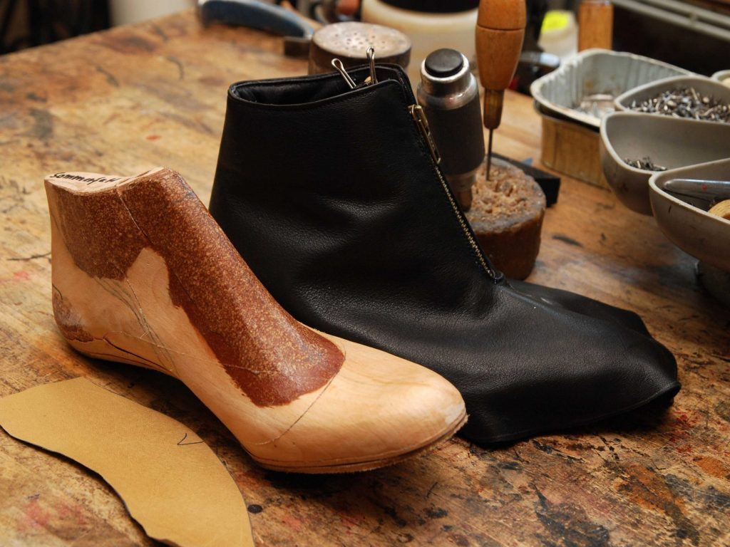 Schuhanfertigung: Leisten und Schäfte werden für den Bodenbau vorbereitet